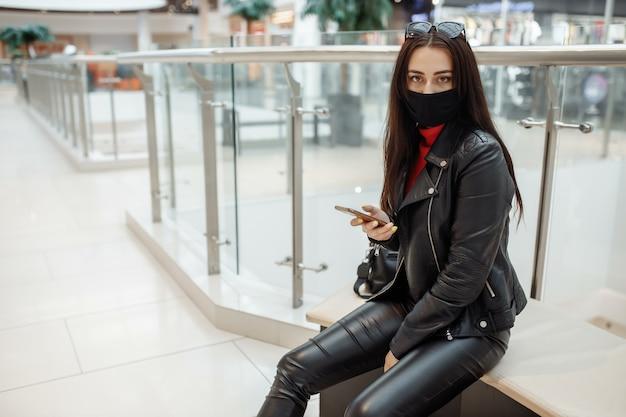 Mädchen mit medizinischer schwarzer maske und handy in einem einkaufszentrum.