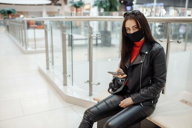 Mädchen mit medizinischer schwarzer maske und handy in einem einkaufszentrum. .