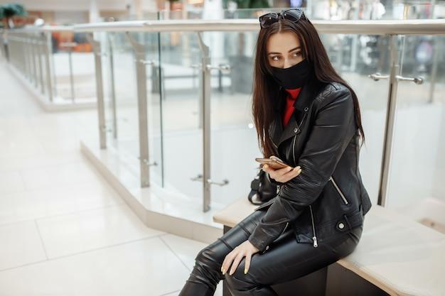 Mädchen mit medizinischer schwarzer maske und handy in einer coronavirus-pandemie des einkaufszentrums