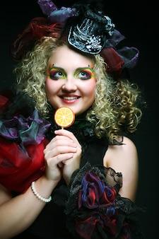 Mädchen mit mit kreativem make-up hält lutscher. puppenstil.