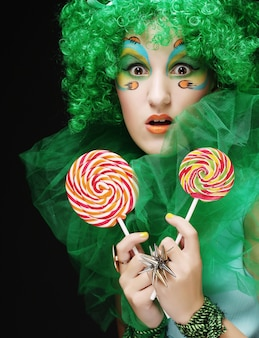 Mädchen mit mit kreativem make-up hält lutscher