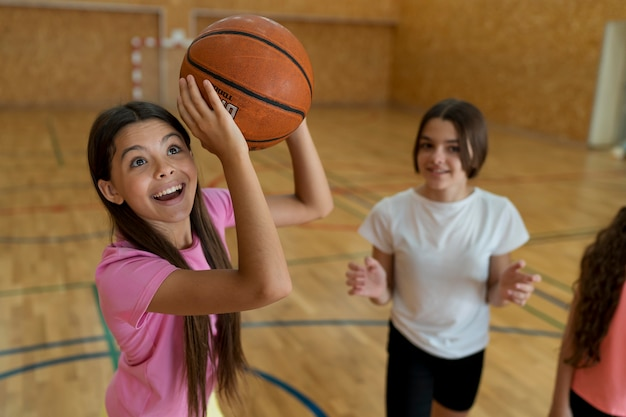 Mädchen mit mittlerem schuss, das basketball hält