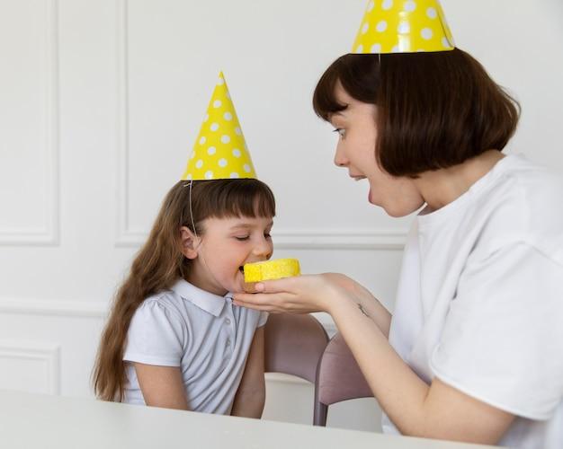 Mädchen mit mittlerem schuss, das cupcake isst