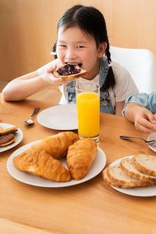 Mädchen mit mittlerem schuss, das isst