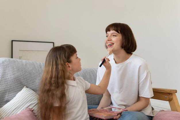 Mädchen mit mittlerem schuss, das make-up-pinsel hält