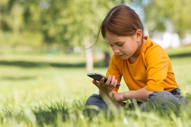 Mädchen mit mittlerem schuss, das smartphone hält