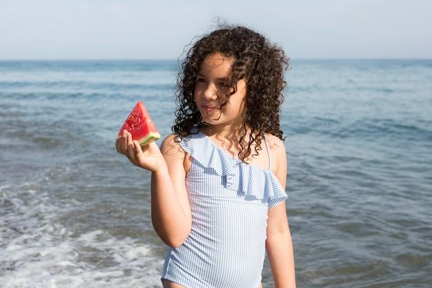 Mädchen mit mittlerem schuss, das wassermelone hält