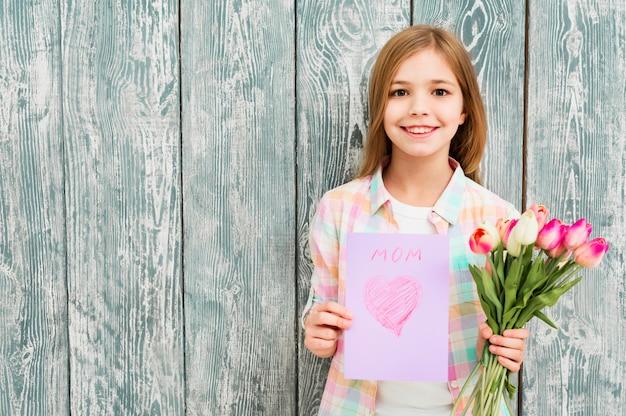 Mädchen mit mutter `s tagespostkarte und tulpen