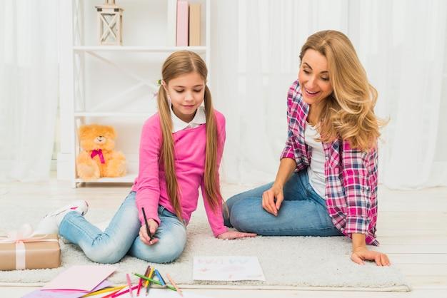 Mädchen mit mutterzeichnung auf papier auf fußboden