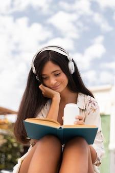 Mädchen mit niedrigem winkel, das draußen liest