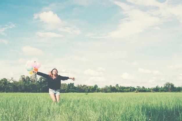 Mädchen mit offenen armen und luftballons