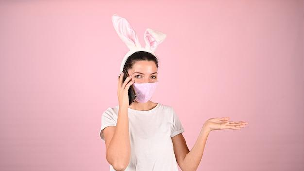 Mädchen mit ohren in einer maske, die am telefon spricht. hochwertiges foto
