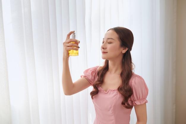 Mädchen mit parfüm, junge schöne frau, die eine flasche parfüm hält und aroma riecht.