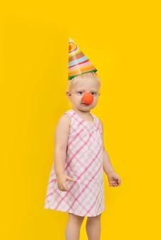 Mädchen mit partyhut auf gelbem grund. vertikaler rahmen.