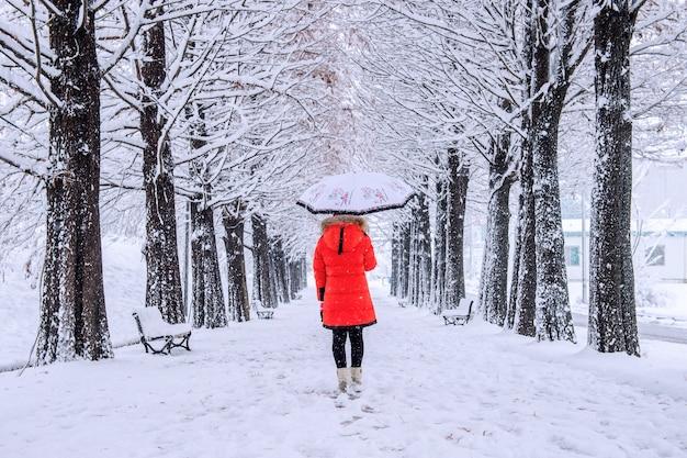 Mädchen mit regenschirm, der auf dem weg und den reihenbäumen geht. winter