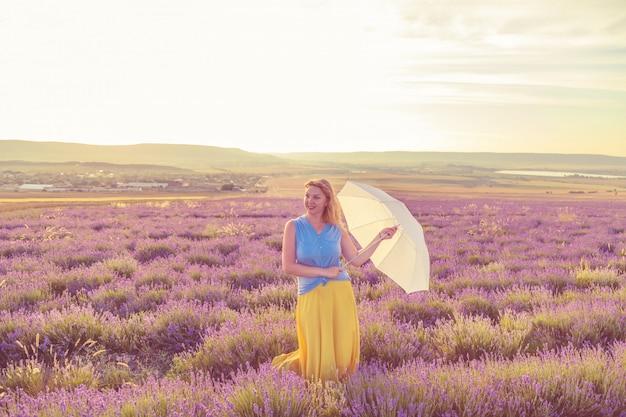 Mädchen mit regenschirm in einem lavendelfeld