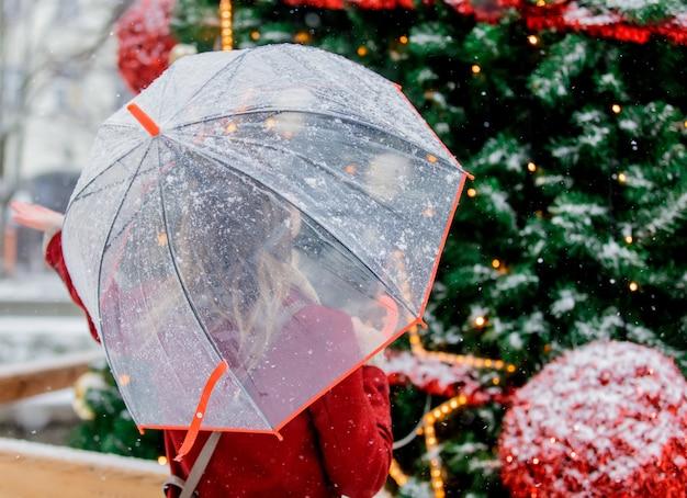 Mädchen mit regenschirm nahe weihnachtsbaum