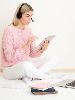 Mädchen mit rosa pullover, der auf digitalem tablett arbeitet