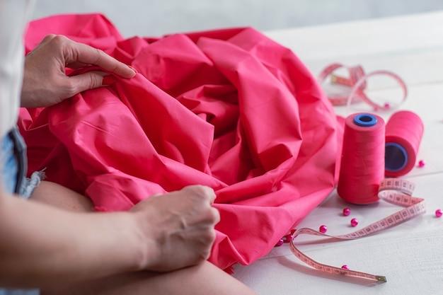 Mädchen mit rosa satingewebe mit fäden und zentimeter auf holzhintergrund mit perlen.