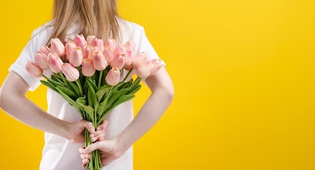 Mädchen mit rosa tulpenblüten isoliert auf gelbem hintergrund mit kopienraumporträt des kindes halten...
