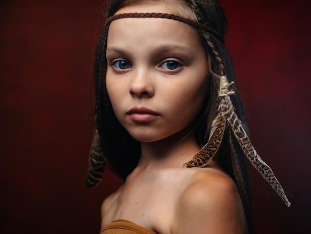 Mädchen mit rotem hintergrund der amerikanischen ethnie der apache-frisur