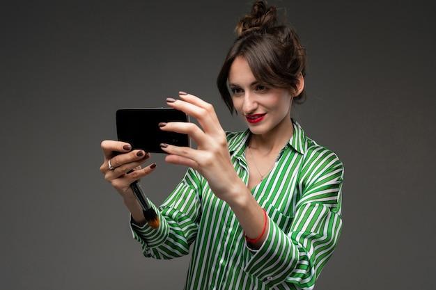 Mädchen mit rotem lippenstift auf den lippen macht selfie an einer dunklen wand
