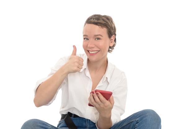 Mädchen mit rotem telefon im weißen hemd und in blue jeans, die sich daumen zeigen. lächelnde frau getrennt auf weiß.