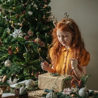 Mädchen mit roten haaren in einem leinenkleid, das ein weihnachtsgeschenk verziert