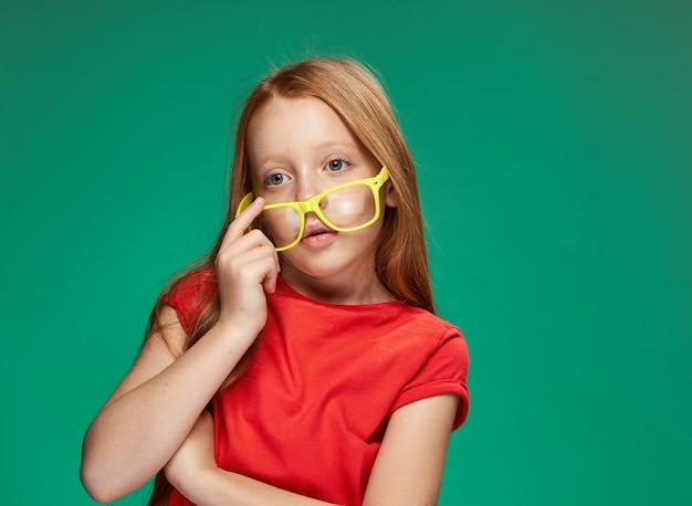 Mädchen mit roten haaren und brillen, die schulgrün trainieren