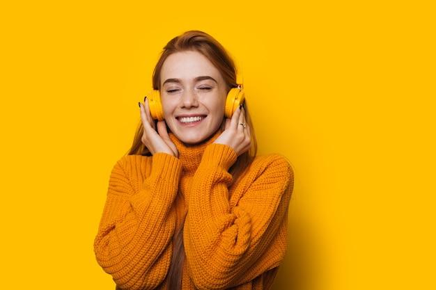 Mädchen mit roten haaren und sommersprossen hört musik mit kopfhörern