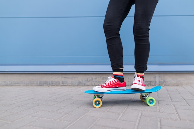 Mädchen mit roten kerlen, die auf einem blauen skateboard gegen eine oberfläche einer blauen wand reiten