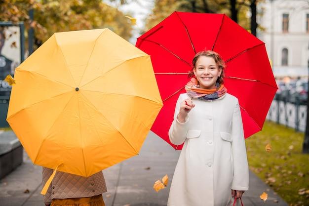 Mädchen mit roten und gelben regenschirmen, die auf der herbststraße der stadt aufeinander zugehen. trockene laub auf der straße.