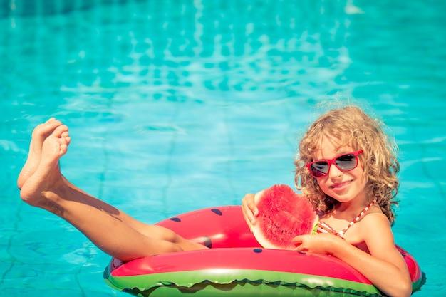 Mädchen mit roter sonnenbrille, die eine wassermelone auf einer aufblasbaren wassermelone im schwimmbad hält