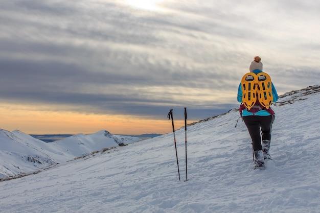 Mädchen mit rucksack in den bergen mit schnee. lifestyle-konzept