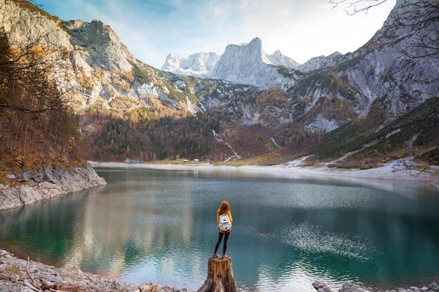 Mädchen mit rucksack steht am ufer eines bergsees