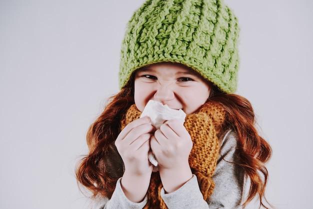 Mädchen mit schal wischt rotz mit serviette ab studioporträt