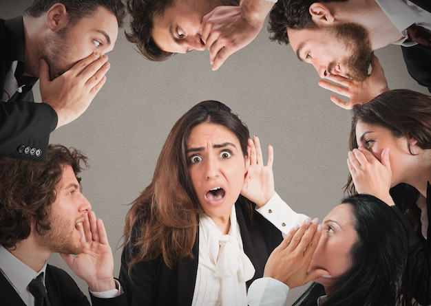 Mädchen mit schockiertem ausdruck, der vielen leuten zuhört