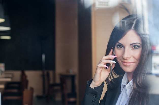 Mädchen mit schönen augen sprechend am telefon