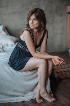 Mädchen mit schönen beinen, die auf dem bett sitzen