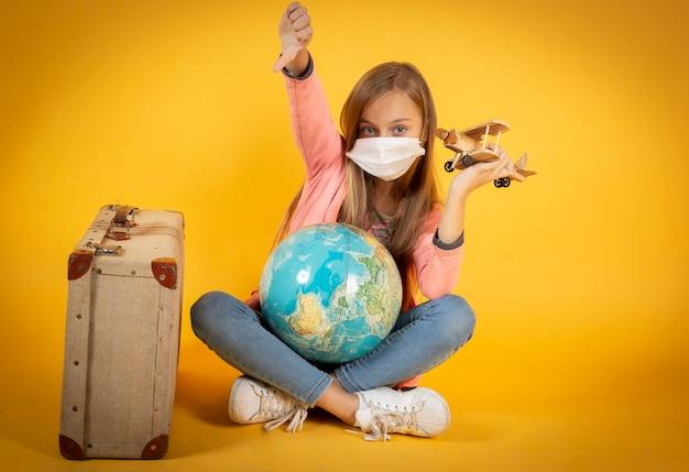 Mädchen mit schutzmaske, koffer, flugzeug und erdkugel, annullierte flüge