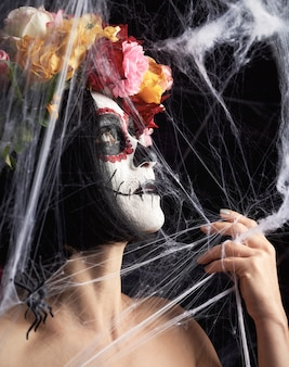 Mädchen mit schwarzen haaren ist in einen kranz aus bunten rosen gekleidet und make-up ist auf ihrem gesicht sugar skull gemacht
