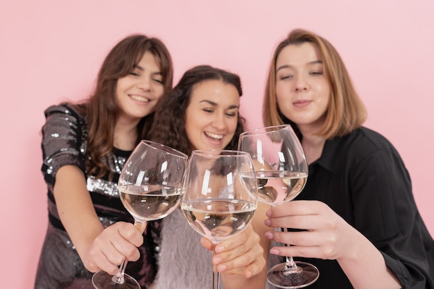 Mädchen mit sektgläsern amüsieren sich auf rosafarbenem hintergrund, weihnachtsfeier.
