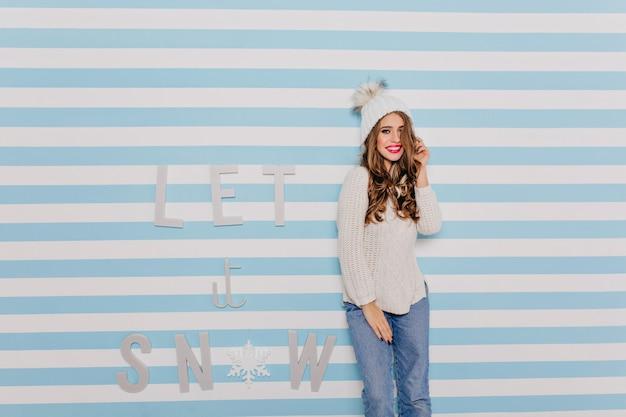 Mädchen mit slawischem aussehen im winterstrickpullover lächelt bescheiden und berührt ihr lockiges dunkles haar. frauenporträt im hellen innenraum