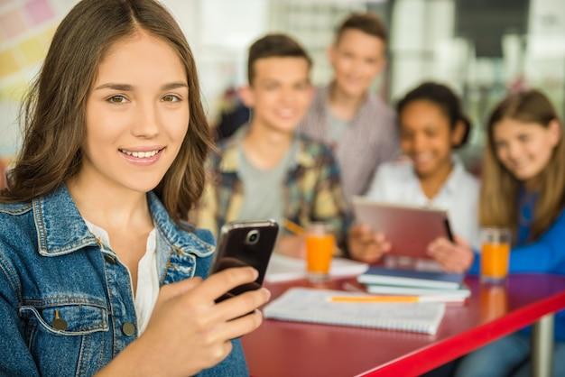 Mädchen mit smartphone schaut in die kamera.