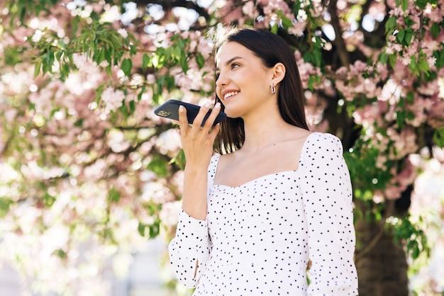 Mädchen mit smartphone-spracherkennung diktiert gedanken-sprachwahlnachricht im freien