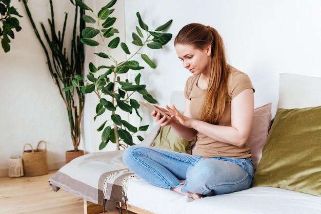 Mädchen mit smartphone zu hause auf sofa spaß gruß online sitzen