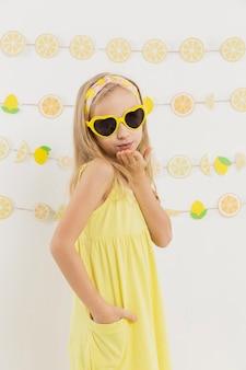 Mädchen mit sonnenbrille, die einen kuss bläst