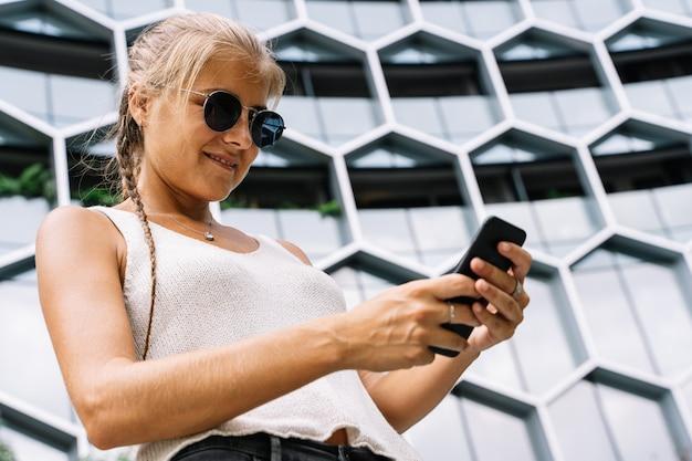 Mädchen mit sonnenbrille, die vor einem modernen gebäude steht, das mit dem handy eine sms sendet
