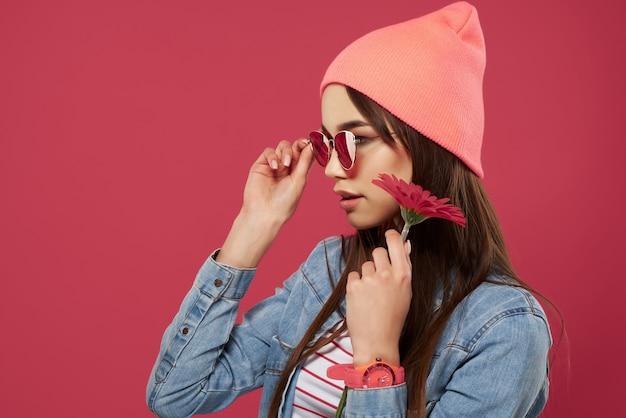 Mädchen mit sonnenbrille trägt einen rosa hut rote blumenmode posiert romantik