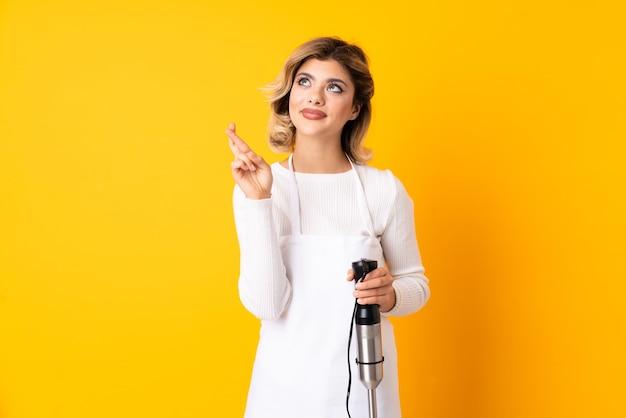 Mädchen mit stabmixer lokalisiert auf gelb mit den fingern, die kreuzen und das beste wünschen